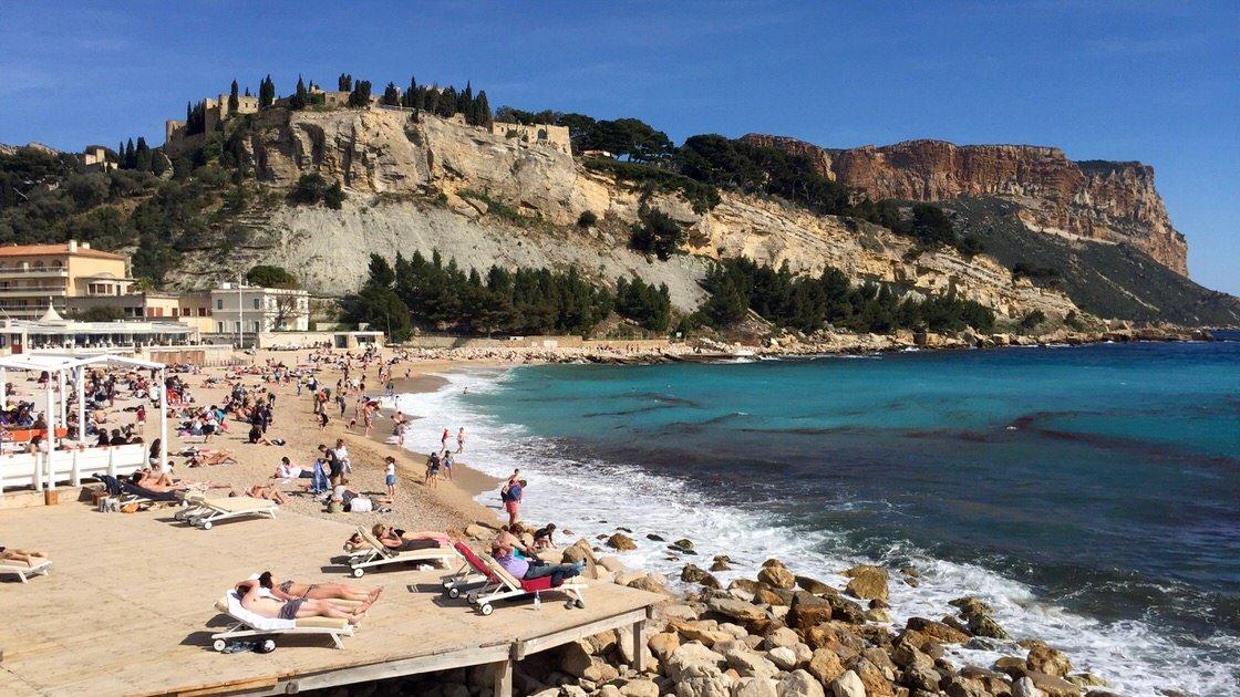 Na pierwszym planie plaża w Cassis, na drugim niewielkie wzgórze z zamkiem - hotelem, a na trzecim planie Cap Canaille