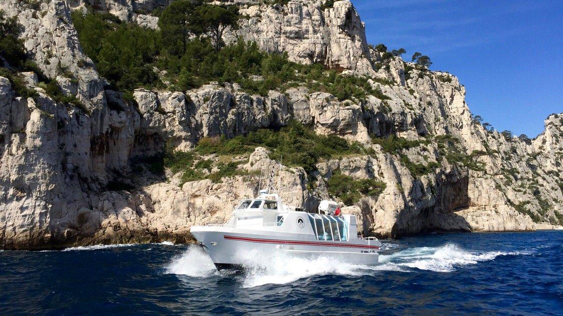 Statek wycieczkowy z turystami zwiedzającymi calanques obok Cassis