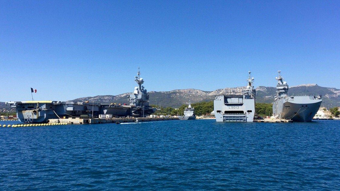 Po lewej lotniskowiec Charles de Gaulle, a po prawej dwa okręty Mistral, port w Tulonie