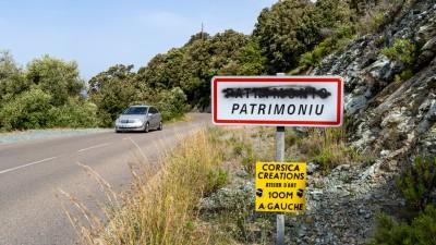 Tablica z zamazaną nazwą miejscowości po francusku, Korsyka