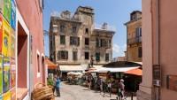 Place Gaffori w Corte. Na budynku w centrum widoczne ślady kul genueńskich